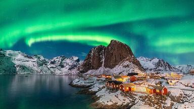 Northern lights above Festhelltinden peak and Hamnoy Norway
