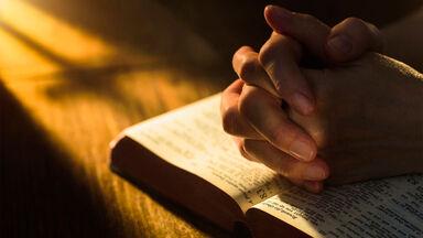 hands praying on Bible Beatitudes