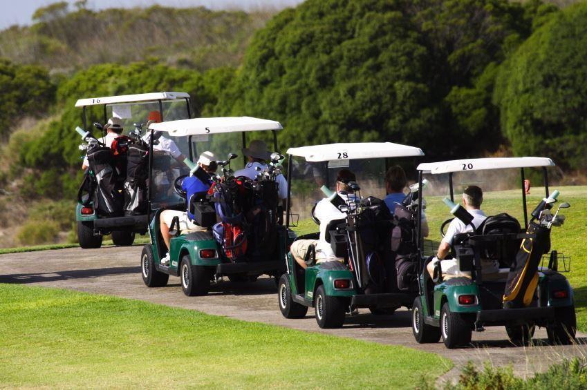 golf carts drive down a path
