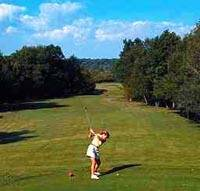 Woman teeing off down a long green