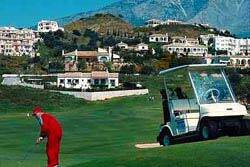 Red-clad golfer and a collection of mountain homes, with his cart beside him
