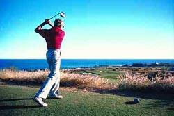 Red-shirted golfer completing a swing, looking away at his drive