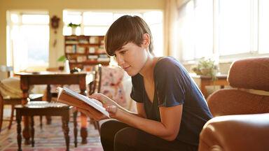girl reading a novella at home