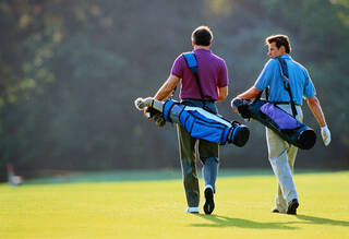 Golfers carrying clubs on course