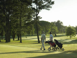 golfers pulling push carts on course