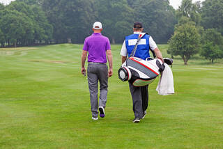 Golfer with caddie on course