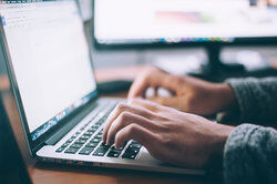 person typing letter on laptop