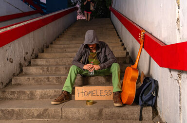 homeless man sitting on stairs