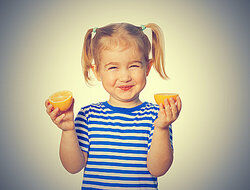 young girl holding orange halves