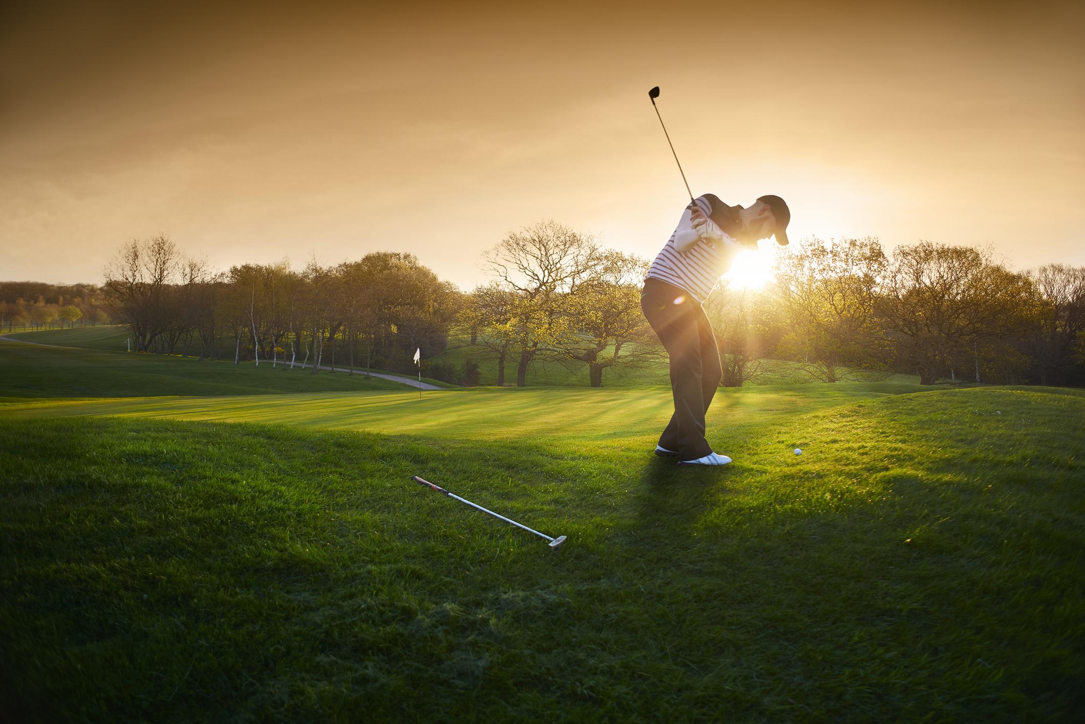 Golfer hits a shot at sunset