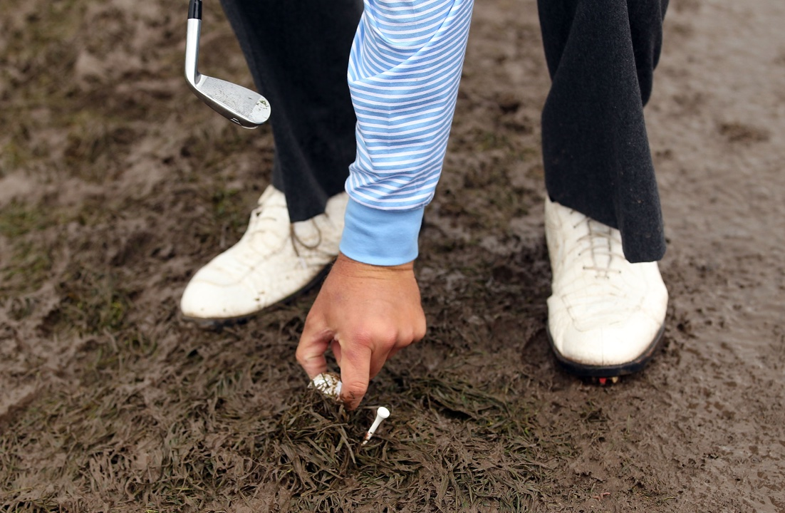 Golfer lifts his ball from mud