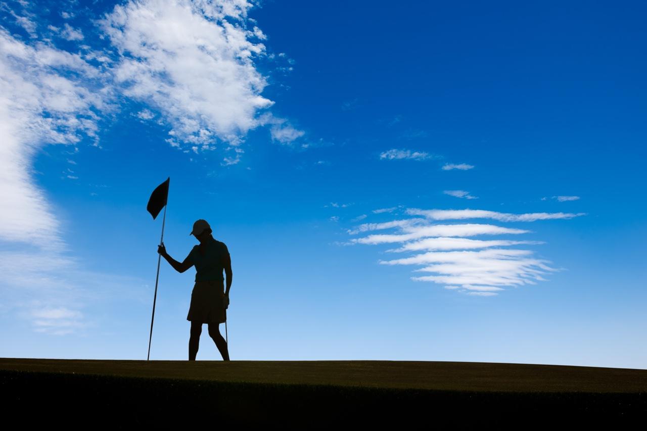 Silhouette of golfer tending the flag