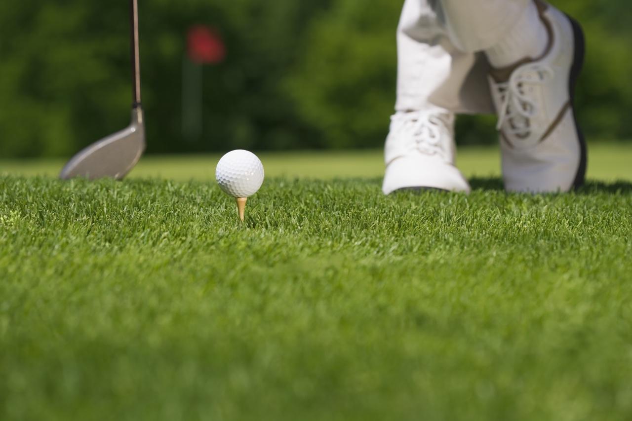 Golfer waits on tee with feet crossed
