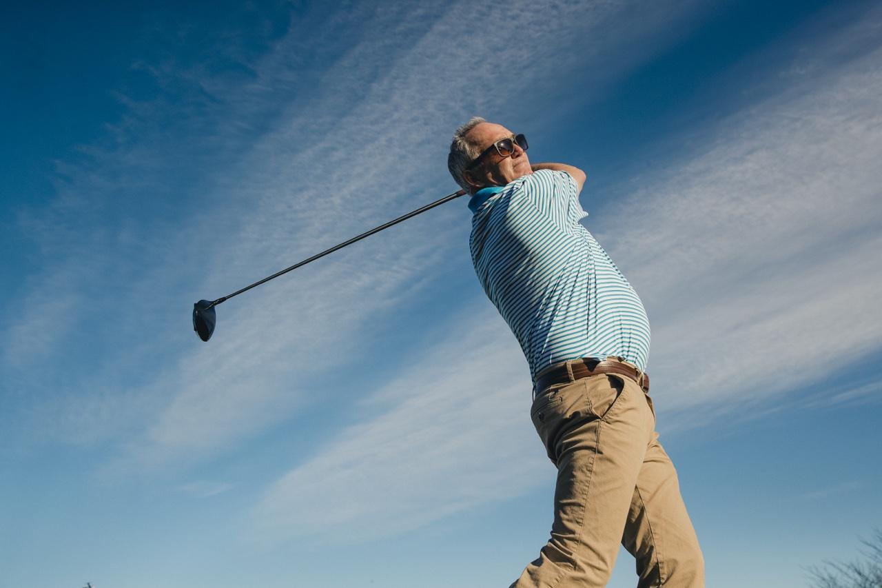 Man holding golf swing follow through