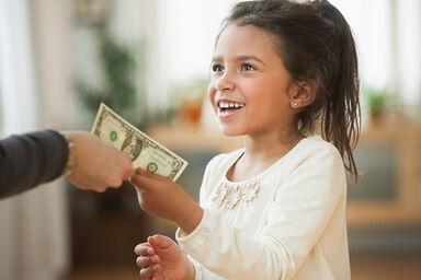 child being handed allowance