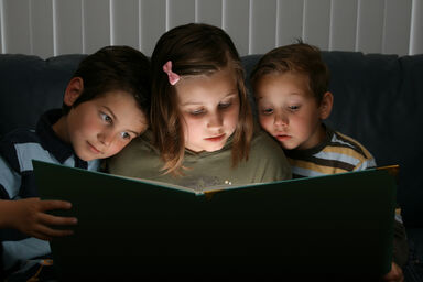 3 children reading a short story together
