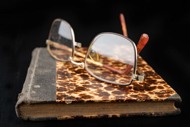 book with tattered cover and spectacles
