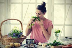 Young woman smelling wild herbs vignette