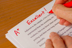 teacher grading A+ on essay paper