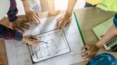 Pointing to architects drawing blueprint