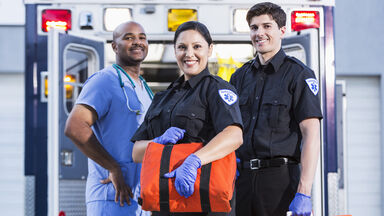 Paramedics standing in front of ambulance