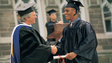 man receiving diploma at graduation