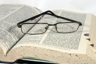 open dictionary with glasses on top