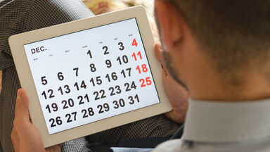 Man holding tablet with calendar image