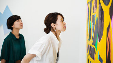 women critique and view art in museum