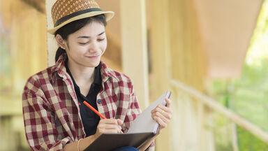woman doing creative writing in book