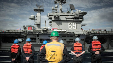 navy soldiers standing against ship