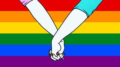 lesbian couple holding hands on lgbt flag