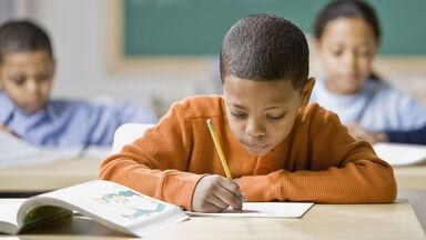Boy practicing adverb worksheet at school