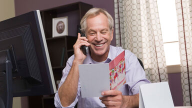 man reading funny retirement card in office