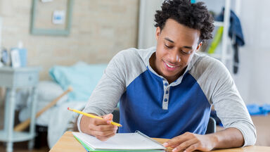 Young man writing thoughtfully