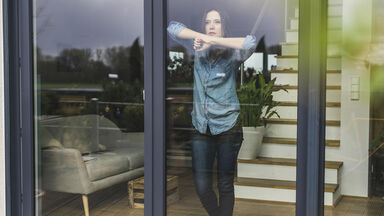 Woman staring out sliding glass doors in isolation
