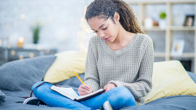 Teen girl writing in journal