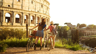 Two woman with bicycles viewing Roman Colosseum