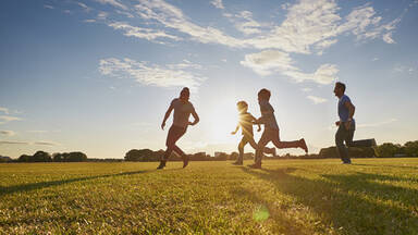 Family running in sunny meadow