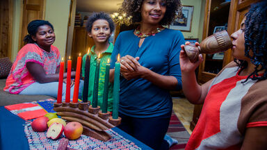 family celebrating with Kwanzaa unity cup