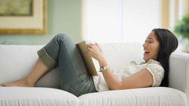 Woman laughing while reading funny literature