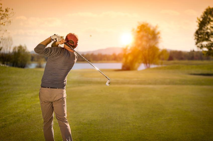 golfer hitting into sunset