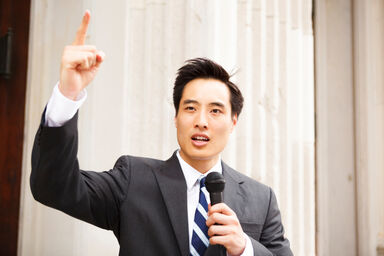 Man waving finger and holding microphone as declamation example