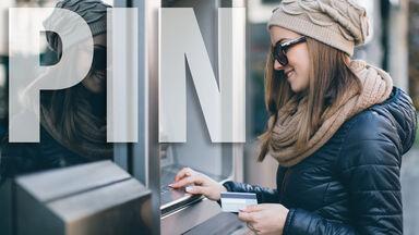 Woman entering PIN at an ATM