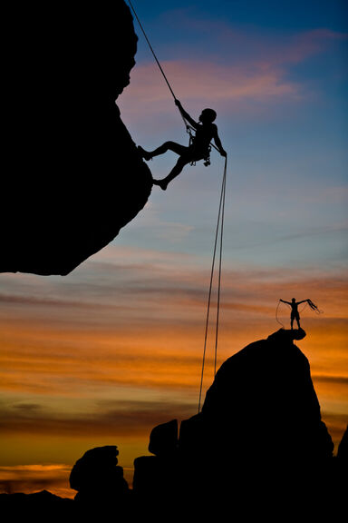 Person using ropes to rock climb as examples of courage