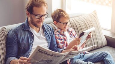 father and son comparing facts opinions reading newspaper