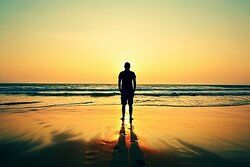 Man standing on a sandy beach as examples of objectivism