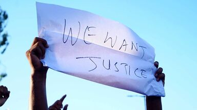 protest sign with words we want justice