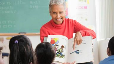 teacher reading picture story book to class