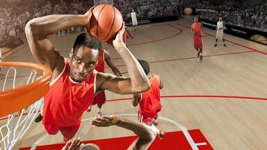 basketball player doing slam dunk on court